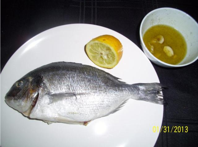Use the remaining half of the lemon to rub down the defrosted Sea Bream.